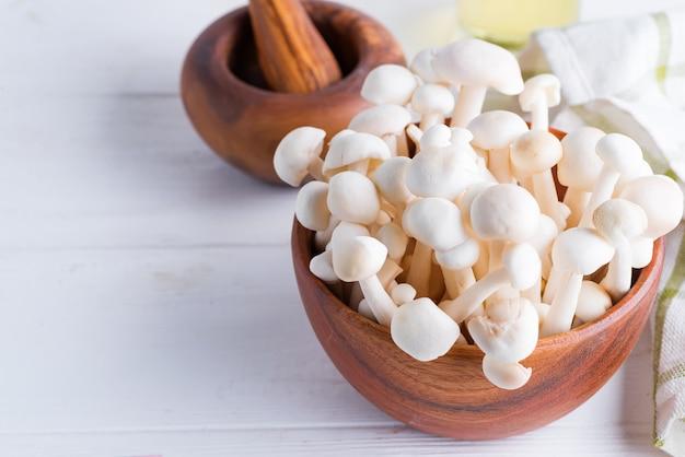 흰색 나무 배경에 올리브 나무로 만든 나무 그릇에 신선한 자연 enoki 버섯.