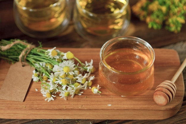 Fresh natural honey in  glass jar,  bunch of chamomile and two cups of herbal tea on  wooden board.