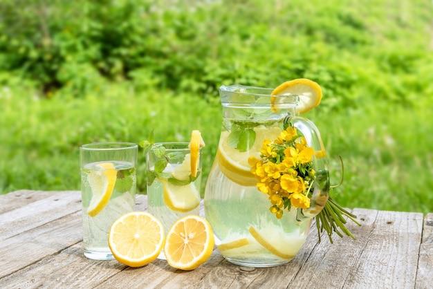 黄色い花の花束と自然のテーブル上のガラスデカンターでスライスしたレモンと新鮮な天然レモネード。