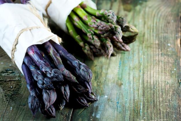 木製の背景に緑と紫のアスパラガス野菜の新鮮な自然有機2バンドル。