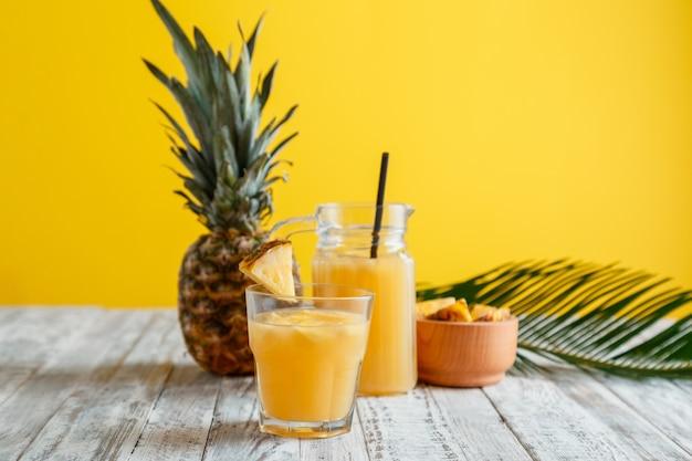 新鮮な天然パイナップルジュースカクテルとパイナップルジュースガラスジャグ、白い木製のテーブル黄色