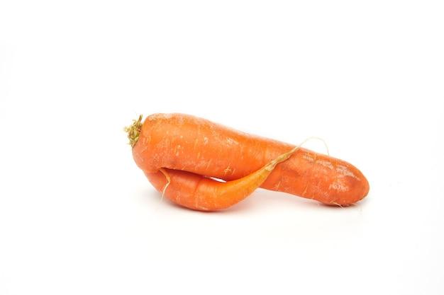 Свежая натуральная уродливая сырая морковь, изолированная на белой стене.