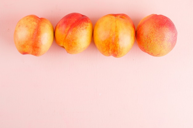 Fresh nectarines on a pink surface. flat lay.