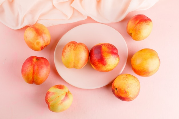 Fresh nectarines in a plate flat lay on pink and textile table