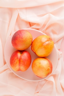 Fresh nectarines in a plate on pink textile surface, high angle view.