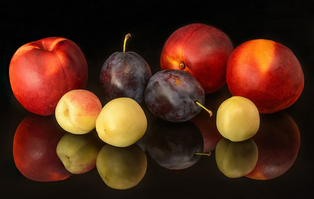 Fresh nectarines and plums on black background