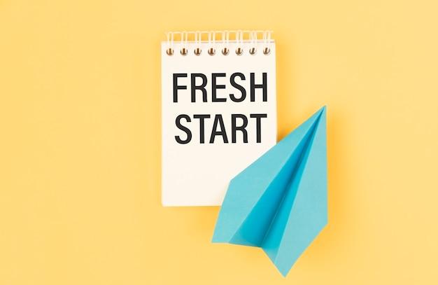 新鮮な新しいスタート、黄色の背景、人生とビジネスの動機付けのインスピレーションの概念に対して本に書かれたテキストの単語のタイポグラフィ