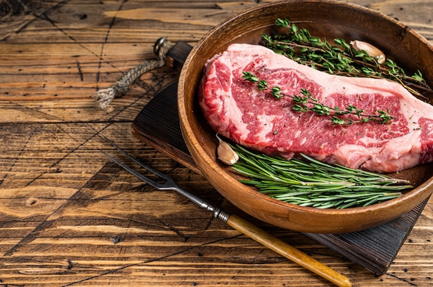 Fresh new york strip beef meat steak or striploin in a wooden plate with herbs