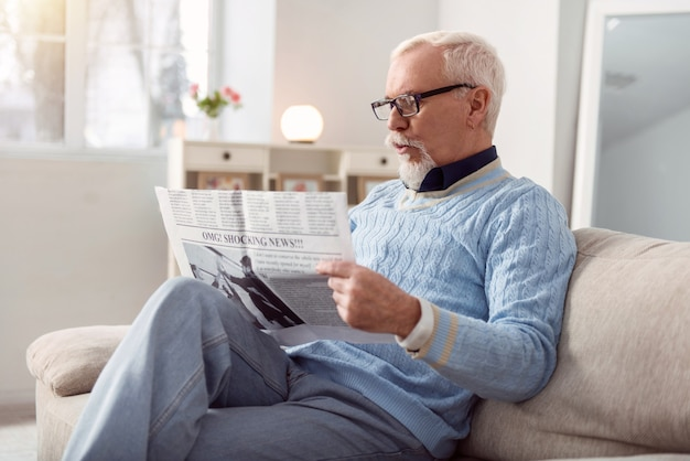 Fresh news. handsome bearded man sitting comfortably on the couch in the living room and reading a newspaper, being surprised by the news in it