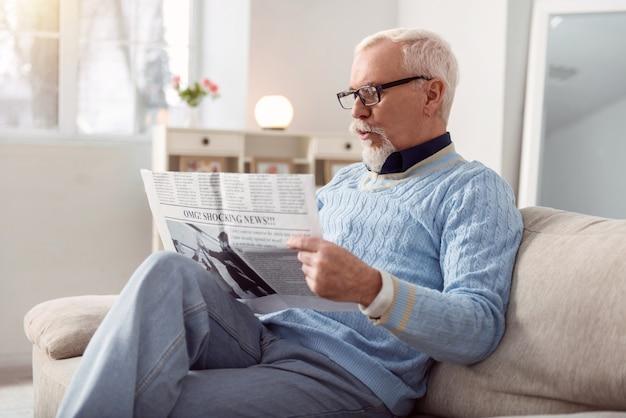 신선한 뉴스. 잘 생긴 수염 난 남자가 거실의 소파에 편안하게 앉아 신문을 읽고 뉴스에 놀란다.