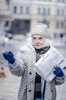 新鮮な新聞。それらを販売しながら新聞のパックを保持している元気のない不幸な女性