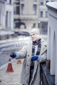 新鮮な新聞。人々にそれを提供しながら朝刊を持っている悲しい不幸な女性