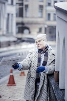 Fresh newspapers. sad unhappy woman holding a morning newspaper while offering it to people