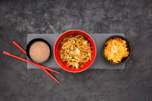 Fresh noodles; sauce and salad served in bowl over black stone background