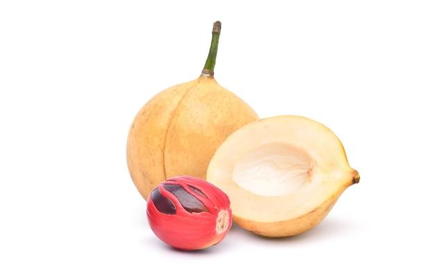 Свежие фрукты мускатного ореха и разрезать пополам и семян, изолированные на белом