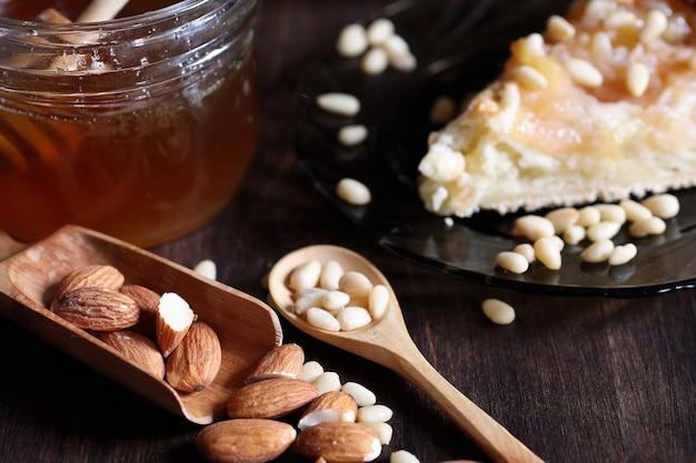 Свежие орехи на столе на завтрак с медом и пирожным