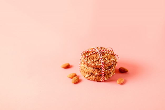 Fresh oatmeal cookies on pink background with copy space, top view.