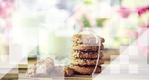 テクスチャウッドの背景にミルクと新鮮なオートミールクッキー。クリスマスのジンジャーブレッドクッキーとミルクのグラス。