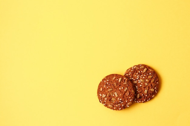 Fresh oatmeal cookies on yellow background board with copy space, top view.