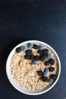 Свежие овсяные хлопья мюсли каша ягоды в тарелке вкусный завтрак
