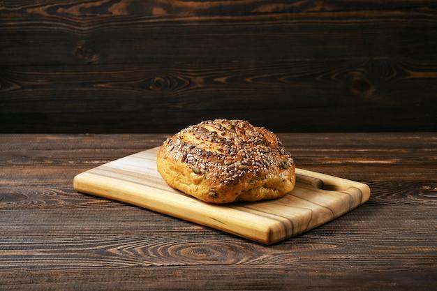 木製のテーブルにヒマワリの種とゴマと新鮮なオーツ麦パン