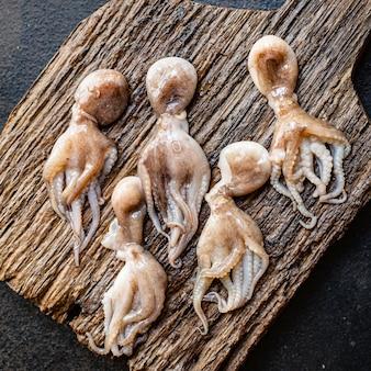Свежий осьминог сырые морепродукты детского размера на столе