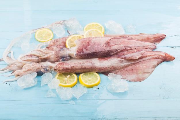 Polpo fresco o calamari crudi su tavola di legno con ingredienti