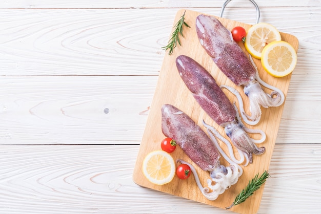 Fresh octopus or squids raw on wooden board