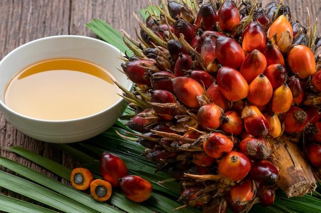 Свежие плоды масличной пальмы и растительное пальмовое масло на пальмовых листьях в деревянных фоне.