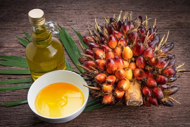 Свежие плоды масличной пальмы и растительное пальмовое масло на пальмовых листьях в деревянном пространстве.