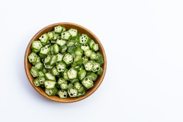 Fresh okra slices in wooden bowl on white background. top view