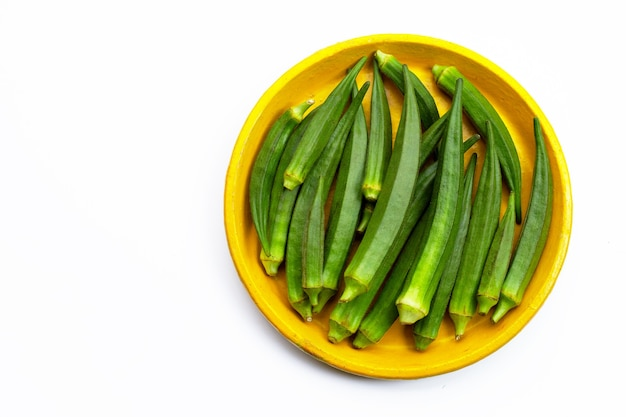 Fresh okra in yellow plate on white background