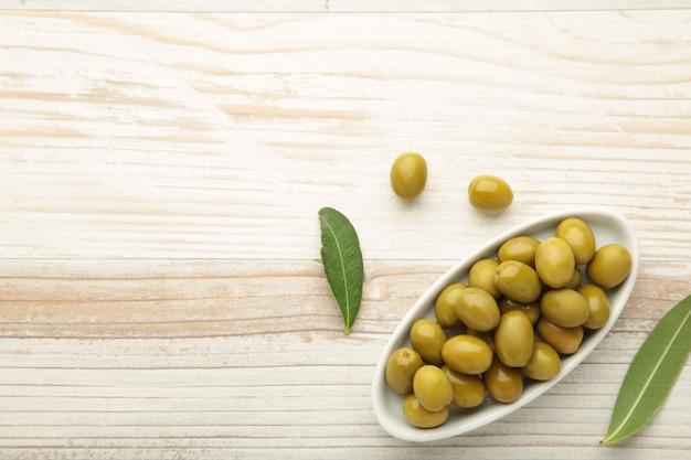 Свежие оливки в миске с листьями на белом фоне с копией пространства.