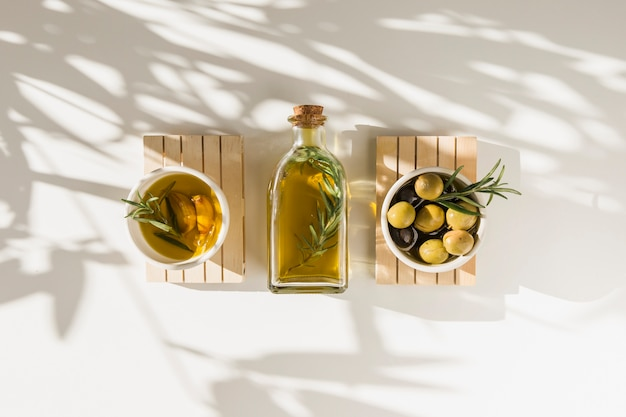 Fresh olives with oil bottle on white backdrop