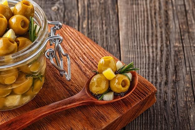 素朴な木製の背景にローズマリー、ニンニク、レモン、オリーブオイルと新鮮なオリーブ