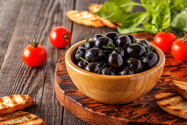 Fresh olives with toasted baguette on a wooden board