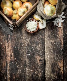 箱と袋に入った新鮮な玉ねぎ。木製の背景に。