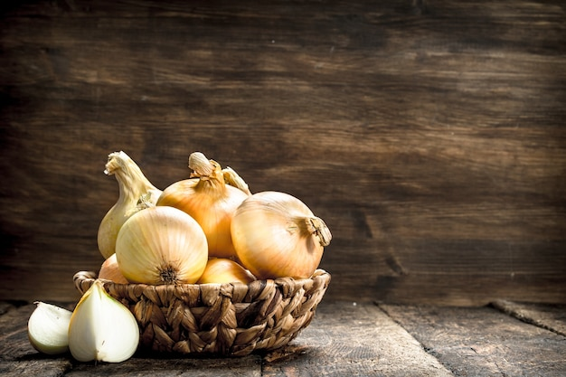 Fresh onions in a basket. on a wooden background.