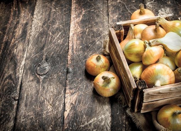 古い箱に入った新鮮な玉ねぎ。木製の背景に。