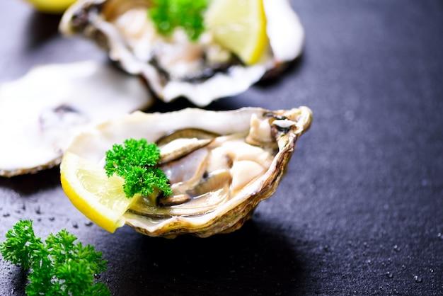 Fresh opened oysters, lemon, herbs, ice on dark metal . top view, copy space