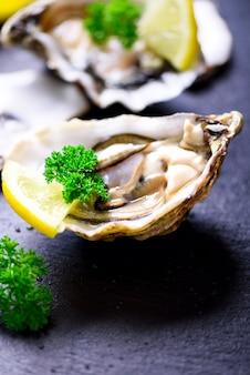 Fresh opened oysters, lemon, herbs, ice on dark metal .