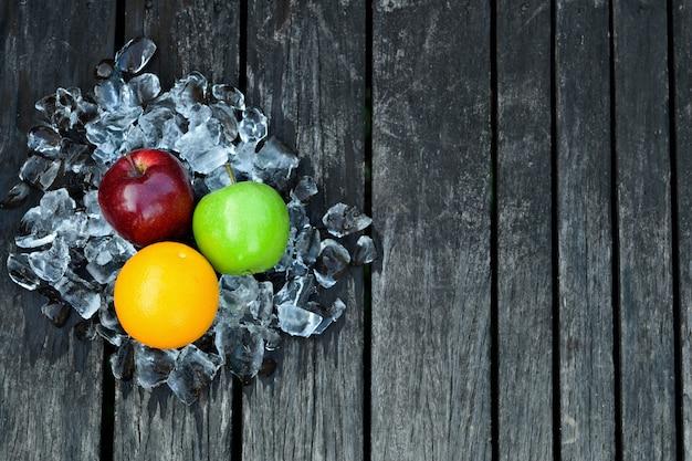 Свежий апельсин и яблоки на кубик льда на деревянный