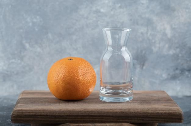 Свежий апельсин и стекло на деревянной доске.
