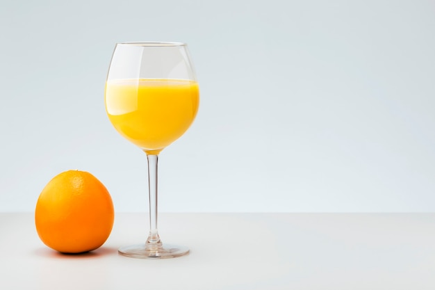 Свежий апельсин и стакан с соком на сером фоне с копией пространства. здоровый витаминный напиток.