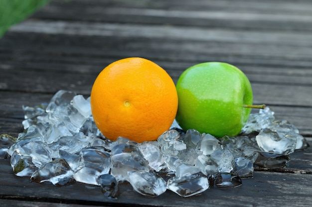 Свежий апельсин и зеленое яблоко на кубик льда на деревянный стол