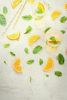 明るい灰色の石の大理石のテーブルの上のグラスに氷と新鮮なオレンジとミントのレモネード