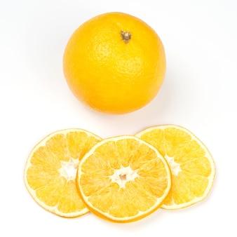 新鮮なオレンジと白い背景の上の乾燥したオレンジの断片。果物の便利なビタミン食品