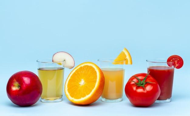 Свежий апельсиновый, яблочный, томатный соки на синем surfce. полезные и натуральные напитки. диета и витамины
