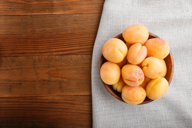 Свежие оранжевые абрикосы в деревянном шаре на деревянном copyspace. вид сверху.