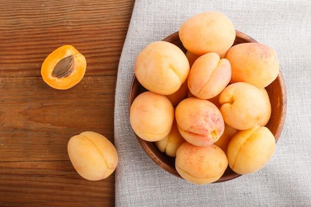 Свежие оранжевые абрикосы в деревянной миске. вид сверху.